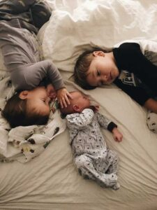 Empathic boy comforting infant brother on bed beside sibling