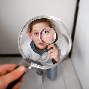 Person holding magnifying glass with white background